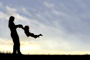 A silhouette of a playful young mother spinning and dancing with her little child outside at sunset on a summer day.